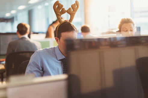 Businessman wearing antler headband in office - CAIF06660