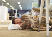 Businessman with pillow and blanket sleeping on office floor - CAIF06666