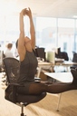 Businesswoman stretching arms overhead with feet up on desk in office - CAIF06672