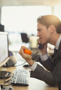 Angry businessman squeezing stress ball and talking on telephone at computer in office - CAIF06675