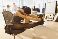 Businesswoman stretching legs with feet up on desk in office - CAIF06678
