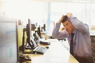 Stressed businessman pulling his hair out at computer in office - CAIF06684