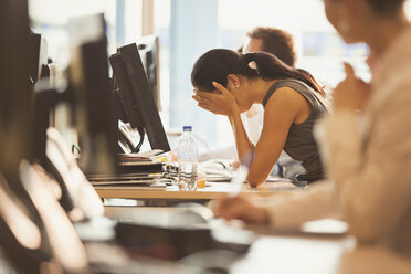 Stressed businesswoman with head in hands at office desk - CAIF06693