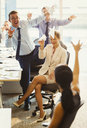Playful business people throwing paper airplanes at each other in office - CAIF06699
