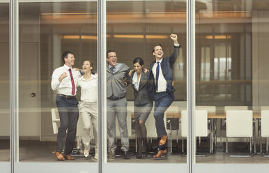 Business people celebrating and cheering at conference room window - CAIF06702