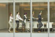 Business people wearing party hats dancing in conga line at conference room window - CAIF06705