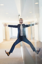 Symmetrical reflection portrait of businessman with arms and legs outstretched in office corridor - CAIF06711