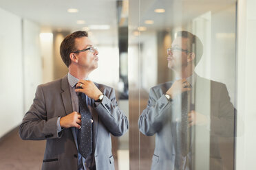 Reflection of confident businessman adjusting tie in office corridor - CAIF06714