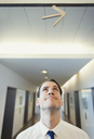 Businessman looking up at arrow overhead - CAIF06717