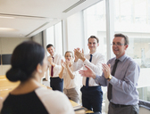 Business people clapping for businesswoman in conference room - CAIF06723