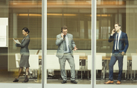 Business people on cell phones and taking notes at conference room window - CAIF06729