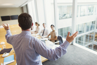 Businessman gesturing to colleagues in conference room meeting - CAIF06735