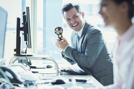 Portrait of enthusiastic businessman holding winner trophy at desk in office - CAIF06741