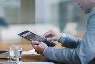 Businessman using digital tablet in office - CAIF06753