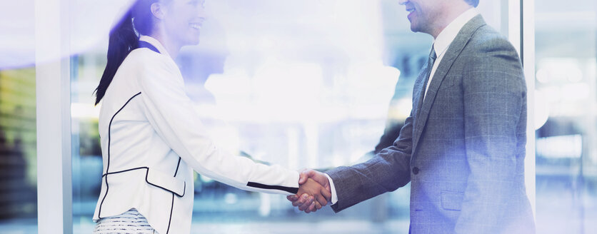 Businessman and businesswoman handshaking in office - CAIF06762