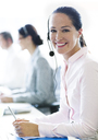 Portrait of smiling businesswoman talking on the phone with headset - CAIF06768