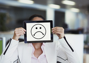 Portrait of businesswoman covering face with digital tablet in office - CAIF06774