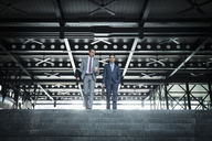 Corporate businessmen with coffee descending modern stairs - CAIF06777