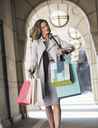 Businesswoman with shopping bags checking wristwatch in cloister - CAIF06801