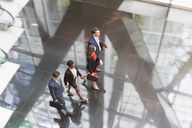 Corporate business people walking in modern office lobby - CAIF06828