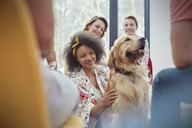 Woman petting dog in group therapy session - CAIF06843