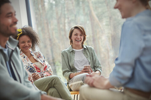 People smiling and laughing in group therapy session - CAIF06846