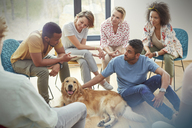 People petting dog in group therapy session - CAIF06858