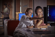 Female businesswomen working late at computer in dark office at night - CAIF06882