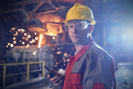 Portrait confident, serious steelworker with walkie-talkie in steel mill - CAIF06906