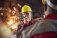 Steelworker talking, using walkie-talkie in steel mill - CAIF06912