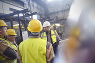 Supervisor and steelworkers talking in meeting in steel mill - CAIF06924