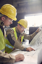 Engineer and steelworker discussing blueprints in steel mill - CAIF06939