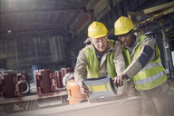 Steelworkers using laptop in steel mill - CAIF06945