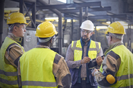 Supervisor talking with steelworkers in steel mill - CAIF06951