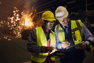 Steelworkers using digital tablets in steel mill - CAIF06954