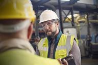 Steelworkers talking in steel mill - CAIF06966