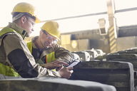 Steelworkers using digital tablet in steel mill - CAIF06981