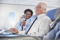 Smiling businessmen exchanging business cards on airplane - CAIF06987