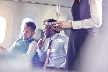 Flight attendant serving champagne to businessmen in first class on airplane - CAIF06990