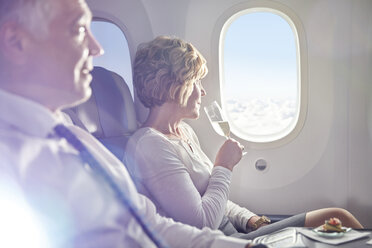Woman drinking champagne in first class, looking out airplane window - CAIF06996