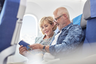 Mature couple reading guidebook on airplane - CAIF06999