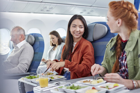 Women friends eating dinner and talking on airplane - CAIF07002