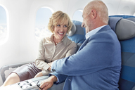 Affectionate mature couple holding hands on airplane - CAIF07005