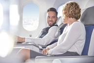 Smiling businessman and businesswoman talking on airplane - CAIF07011