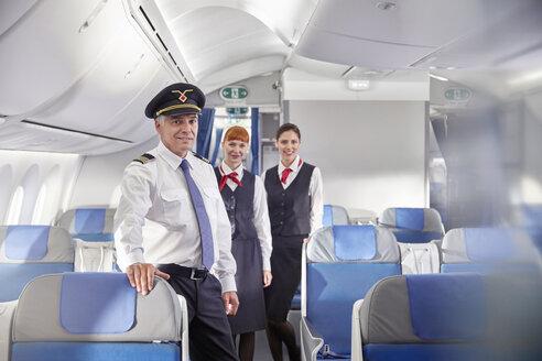 Portrait confident pilot and flight attendants on airplane - CAIF07029