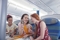 Young women friends laughing, drinking champagne in first class on airplane - CAIF07035