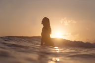 Indonesia, Lombok, female surfer sitting on surfboard at sunset - KNTF01083