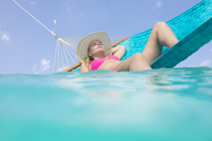 Woman relaxing on a hammock in the sea - ZEF15174