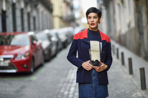 Portrait of fashionable young woman with camera on the street - JSMF00090