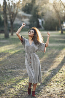 Fashionable young woman dancing in a park in the evening - JSMF00097